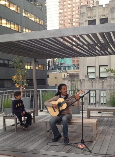 Joao Luiz plays the guitar for a little fan
